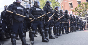 SAN DIEGO USA - MAY 27 2016: Riot police in full tactical gear stand ready to confront protesters at a Trump rally at the San Diego Convention Center