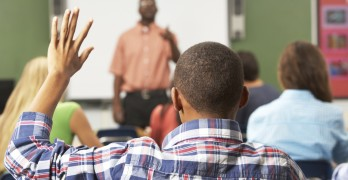 Male Pupil Raising Hand In Class