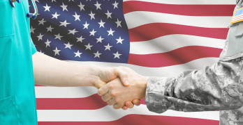 Soldier And Nurse Shaking Hands. Flag On Background - United St