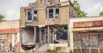 DETROIT USA - JUNE 9 2015: A burned out and semi-demolished building between two closed storefronts on Hamilton Avenue in Detroit Michigan is symbolic of the urban blight that is emblematic of the city.
