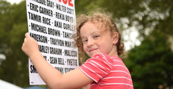 NEW YORK CITY - JULY 18 2015: Hundreds rallied in Cadman Plaza Brooklyn to mark the one year anniversary of Eric Garner's death at the hands of NYPD. Young activist with sign in Cadman Plaza