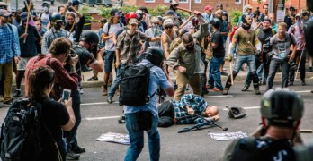 "CHARLOTTESVILLE, NY - August 12, 2017:    Members of the media photograph a counter protestor beating a man associated with the Unite the Right rally's White Nationalist group just outside the perimeter of Emancipation Park during clashes prior the state police and National Guard forcing all to leave the park before a scheduled rally by the Alt -Right movement led by Richard Spencer and other key figures. The entire ""Unite the Right"" rally was to be held over controversy and anger of a possible takedown of the statue of the confederate general Robert E. Lee from the American Civil War.  Credit: Mark Abramson"