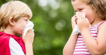 Kids with hay fever or the flue sneezing and cleaning nose with