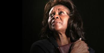 A spiritual black woman clutching her bible and looking toward heaven