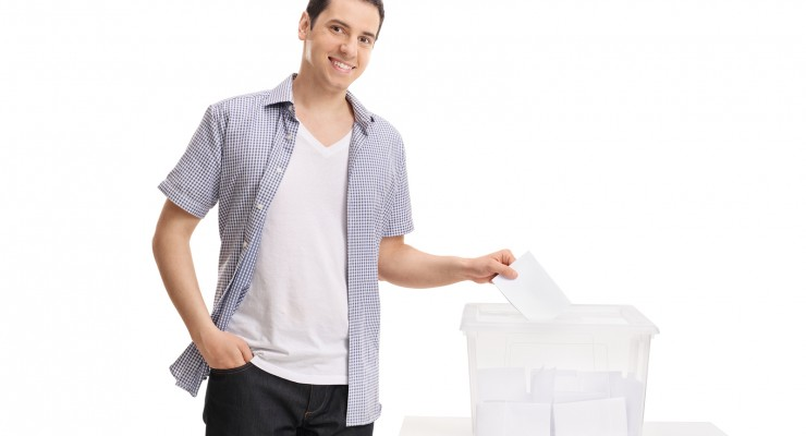 Male voter casting a vote into a ballot box isolated on white ba