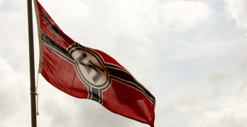 Nazi Germany flag blowing in breeze on flagpole.