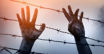 Refugee men and fence. Refugee concept
