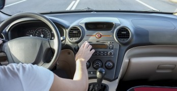 Woman Pressing Cd Audio Eject Button While She Is Driving. Cause