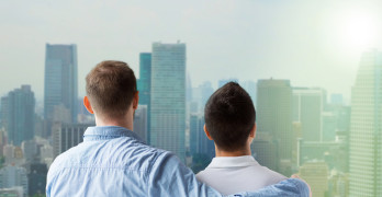 people, homosexuality, same-sex marriage, gay and love concept - close up of happy male gay couple or friends hugging from back over city background