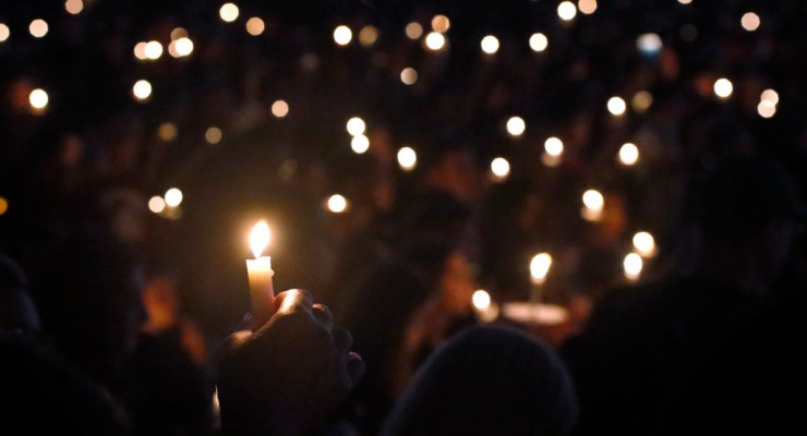 Attendees hold up their candles at a candlelight vigil for the victims of the shooting at Marjory Stoneman Douglas High School, Thursday, Feb. 15, 2018, in Parkland, Fla. The teenager accused of using a semi-automatic rifle to kill more than a dozen people and injuring others at a Florida high school confessed to carrying out one of the nation's deadliest school shootings and concealing extra ammunition in his backpack, according to a sheriff's department report released Thursday. (AP Photo/Wilfredo Lee)