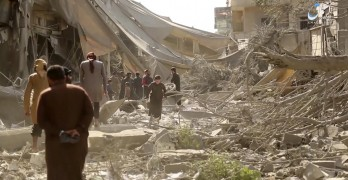 This undated frame grab from video posted online Monday, May 29, 2017, by the Aamaq News Agency, a media arm of the Islamic State group, shows people inspecting damage from airstrikes and artillery shelling in the northern Syrian city of Raqqa, the de facto capital of the IS. Airstrikes have intensified over the past days as U.S.-backed fighters have marched toward the city, getting closer to besieging it from all sides. (Aamaq News Agency via AP)